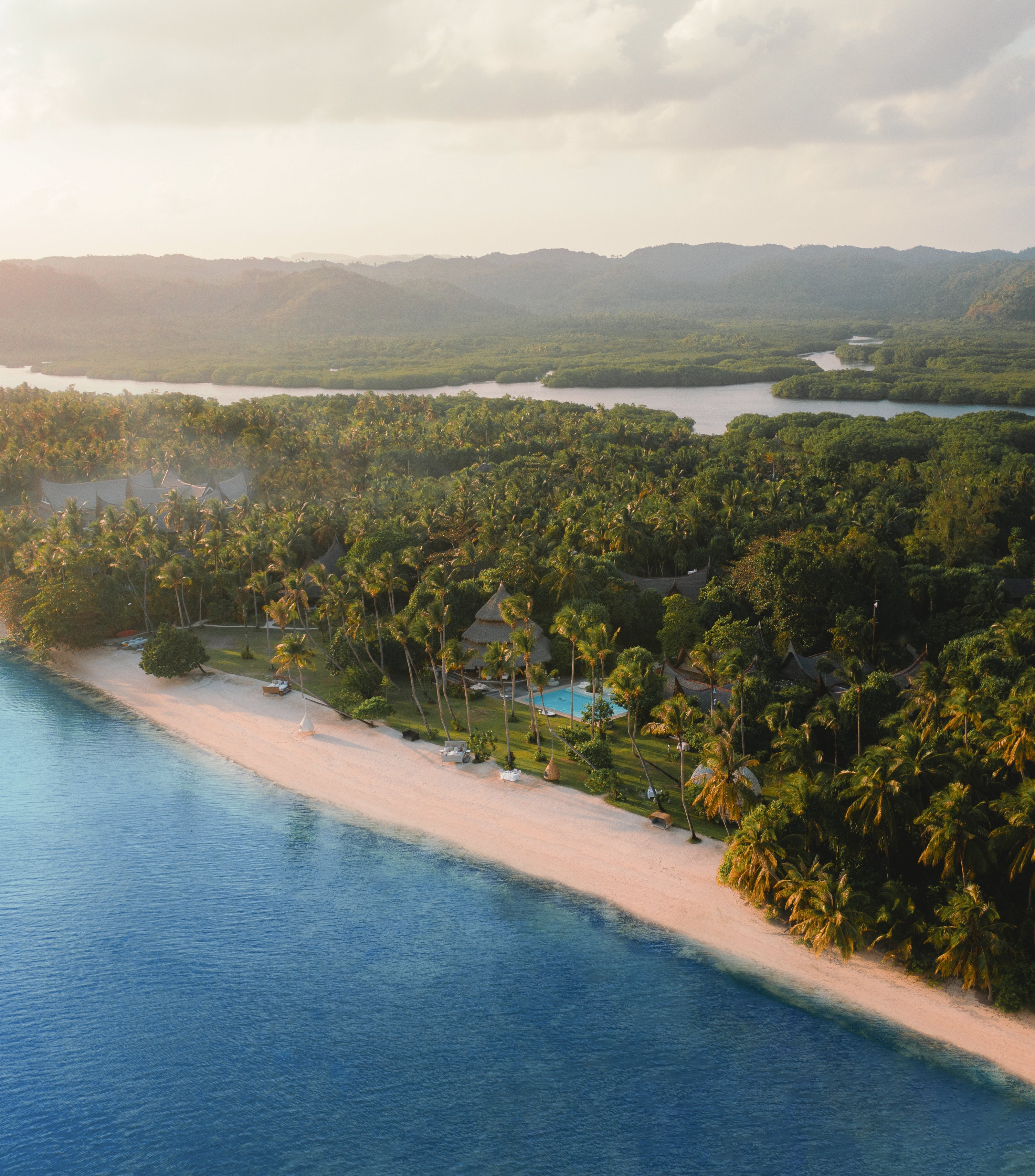 An aerial shot of Nay Palad Hideaway on Siargao Island, Philippines. This regenerative resort has a plastic-free policy and is active in coastal cleanups and mangrove reforestation.